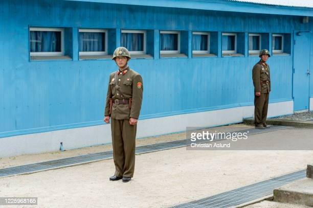 north korean soldiers, standing guard at the joint security area (jsa) seen from the north korean side of the military demarcation line (mdl) at panmunjom. the demilitarized zone (dmz) is the border between north and south korea - military demarcation line korea stock pictures, royalty-free photos & images