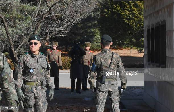 TOPSHOT North Korean soldiers stare at South Korean soldiers at the truce village of Panmunjom in the Demilitarized zone dividing the two Koreas on...