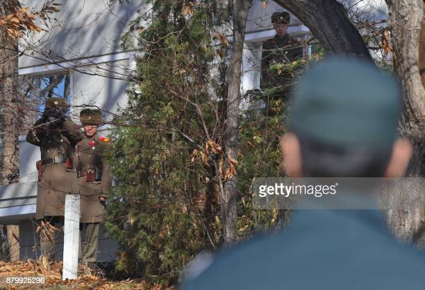 North Korean soldiers stare at South Korean soldiers at the truce village of Panmunjom in the Demilitarized zone dividing the two Koreas on November...