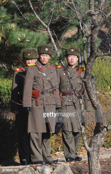 North Korean soldiers stare at the South side at the truce village of Panmunjom in the Demilitarized zone dividing the two Koreas on November 27 2017...