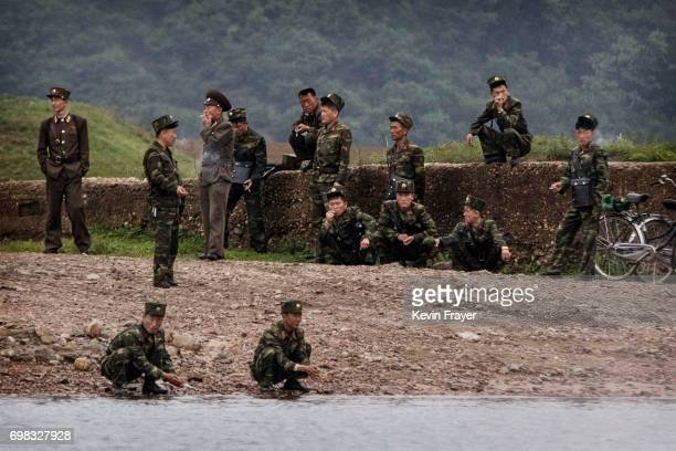 North Korean soldiers wait for a local ferry to cross the Yalu river north of the border city of Dandong Liaoning province northern China near...