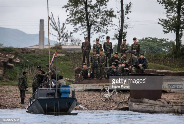 North Korean soldiers wait to ride on a boat used as a local ferry to cross the Yalu river north of the border city of Dandong Liaoning province...
