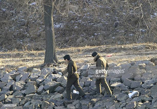 North Korean soldiers walk along the bank of the Yalu River in the North Korean town of Sinuiji, on December 22 in this picture taken from the...
