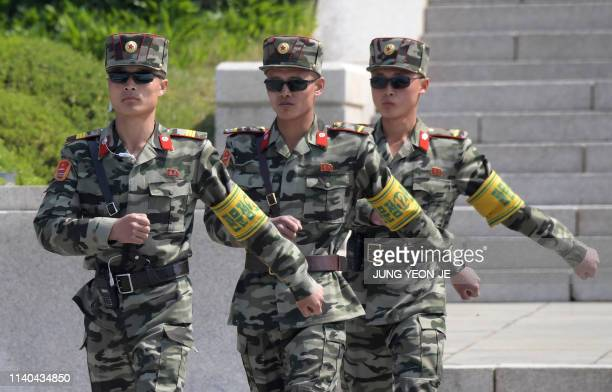 North Korean soldiers walk on the North side at the border truce village of Panmunjom in the Demilitarised Zone dividing the two Koreas on May 1,...