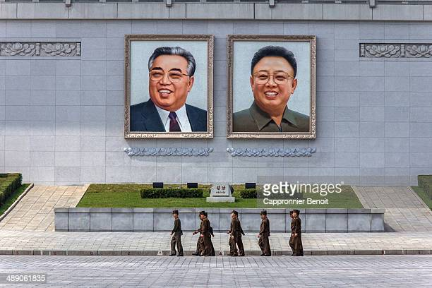 CONTENT] North Korean soldiers walking in front of giant portraits of Kim IlSung and Kim Jungil on Kim IlSung square Pyongyang North Korea