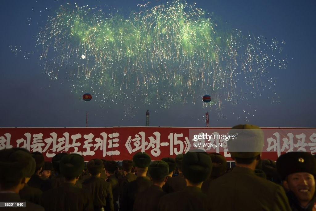 North Korean soldiers watch a fireworks display put on to celebrate the North's declaration on November 29 it had achieved full nuclear statehood, during a mass rally on Kim Il-Sung Square in Pyongyang on December 1, 2017. North Korea's leader Kim Jong-Un declared the country had achieved a 'historic cause' of becoming a nuclear state, its state media said on November 29, after the country tested an intercontinental ballistic missile earlier in the day. / AFP PHOTO / Kim Won-Jin