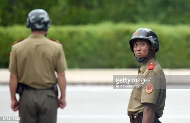 North Korean soldiers watch the South side as the United Nations Command officials visit after a commemorative ceremony for the 64th anniversary of...