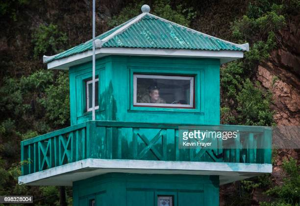 A North Korean soldiers watches from a tower on the Yalu river north of the border city of Dandong Liaoning province northern China near Sinuiju...