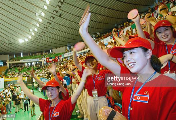 North Korean spectators wave during a volleyball match between North Korea and Denmark at the World Student Games August 21 2003 in Daegu South Korea...
