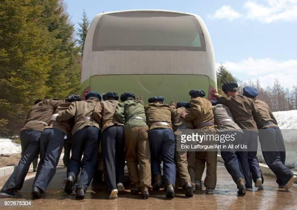 North Korean students pushing a bus out of order Ryanggang Province Samjiyon North Korea on May 3 2010 in Samjiyon North Korea