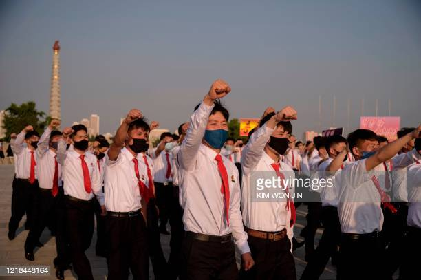 North Korean students take part in a rally denouncing 'defectors from the North' as they march from the Pyongyang Youth Park Open-Air Theatre to Kim...