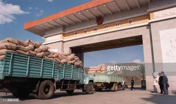 North Korean trucks loaded with sacks of maize wait for clearance 06 May at the Chinese border to cross the Tumen River into the city of Namyang in...
