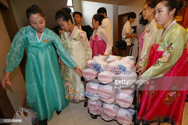 North Korean waitresses wearing traditional cloths 'hanbok' prepare for lunch for separated families during a separated family reunion meeting at the...