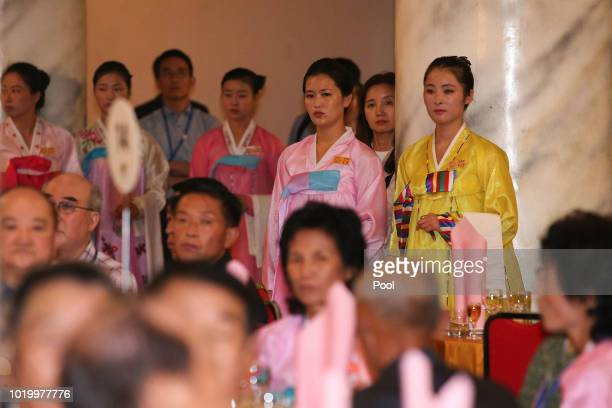 North Korean waitresses wearing traditional cloths 'hanbok' stand during a dinner for separated family reunion meeting at the Mount Kumgang resort on...