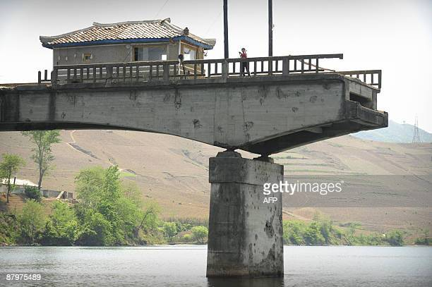 North Korean waves from a bridge destroyed during the Korean war across the Yalu River in North Korea over 60 km northeast of Dandong, in northeast...