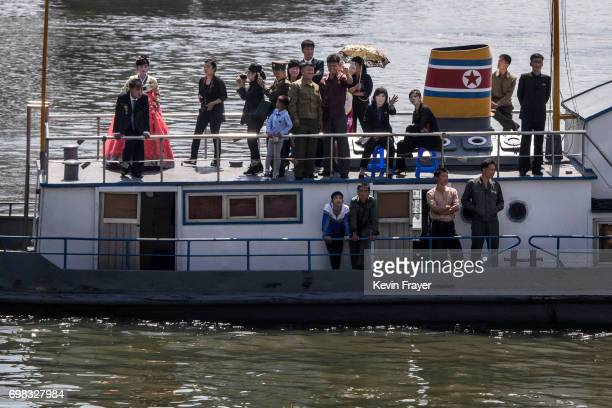 A North Korean wedding party rides a boat on the Yalu river in the border city near Dandong Liaoning province northern China across from the city of...
