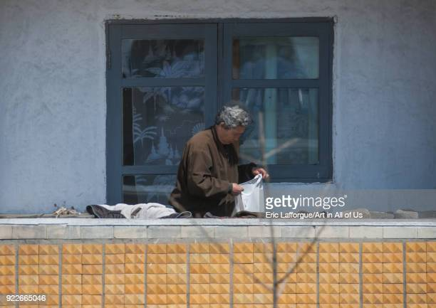 North Korean woman cleaning clothes on her balcony Pyongan Province Pyongyang North Korea on April 29 2010 in Pyongyang North Korea