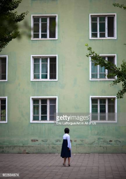 North Korean woman passing in front of a green apartments building Pyongan Province Pyongyang North Korea on September 9 2011 in Pyongyang North Korea