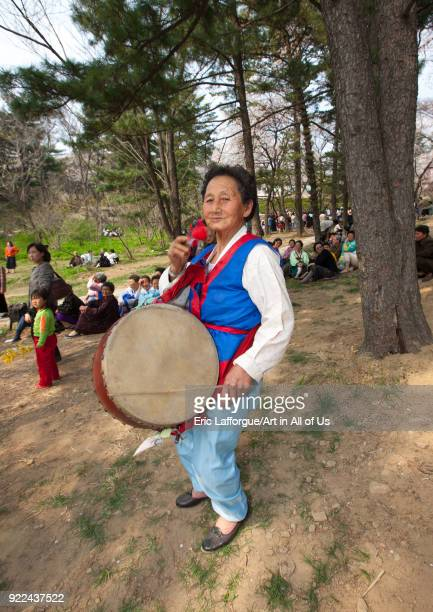 North Korean woman playing drum in a park for the day of the sun which is the birth anniversary of Kim Ilsung Pyongan Province Pyongyang North Korea...