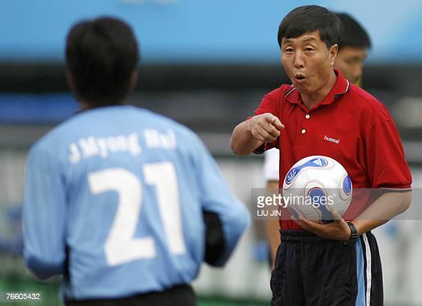 North Korean women's football team head coach Kim Kwang Min gives instructions to goalkeeper Jon Myong Hui during a training session in Chengdu in...