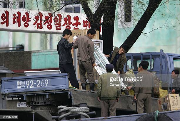 North Korean workers load goods imported from China on a truck on the banks of the Yalu River in the North Korean town of Sinuiju opposite the...