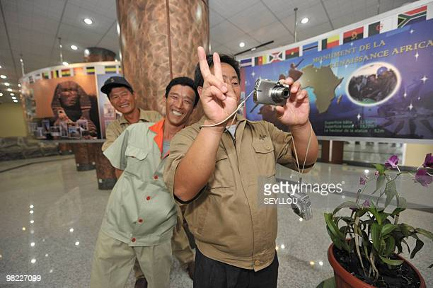 North Korean workers take pictures in the hall of the 'African Renaissance Monument' on April 2 2010 in Dakar on the eve of the inauguration where...