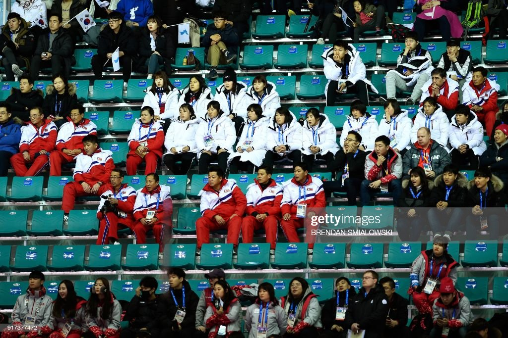 TOPSHOT - North Koreans and other spectators watch the women's preliminary round ice hockey match between Sweden and Unified Korea during the Pyeongchang 2018 Winter Olympic Games at the Kwandong Hockey Centre in Gangneung on February 12, 2018. / AFP PHOTO / Brendan Smialowski