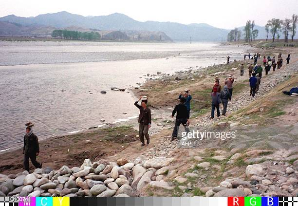 North Koreans carry rocks on their heads as they repair a riverbank 24 April in the wake of flooding which has destroyed thousands of acres of crops...