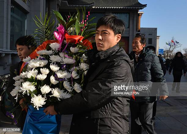 North Koreans carrying flowers as they arrive at the North Korean Consulate in the Chinese border town of Dandong to pay their respects during the...