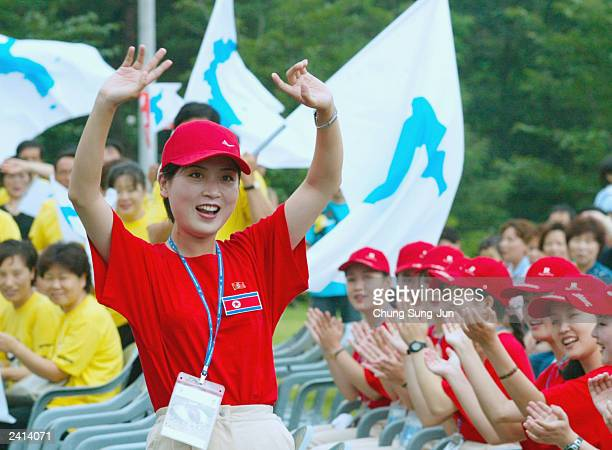 North Koreans cheer as South Koreans wave unified Korean peninsula flags during a welcome ceremony at the World Student Games August 21 2003 in Daegu...