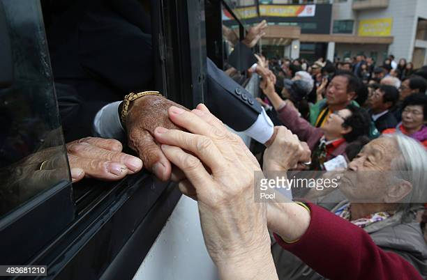 North Koreans in a bus bid farewell to their South Korean relatives before they return to their home after a family reunion having been separated for...