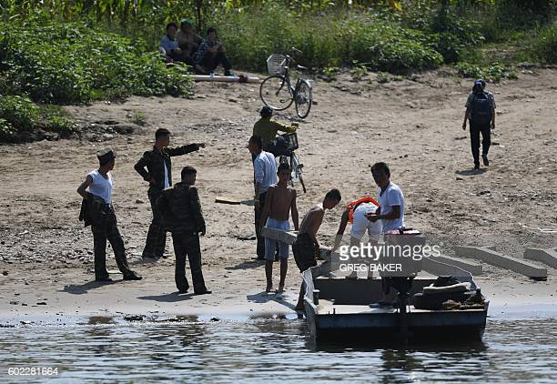 North Koreans load a boat on the bank of the Yalu river near the North Korean town of Sinuiju opposite the Chinese border city of Dandong on...
