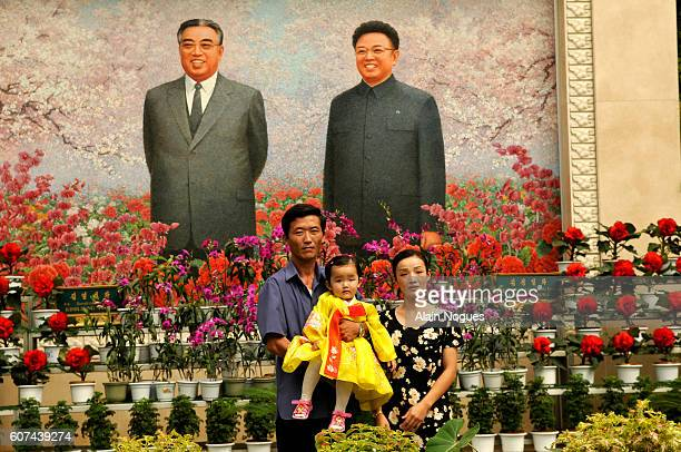 North Koreans pose for a family portrait in front of portraits of President Kim Il Sung and his son Kim Jong Il