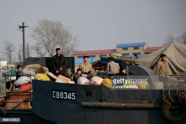 North Koreans ride a boat in Yalu River, the border river shared with China, in Sinuiju, North Korea as seen from across the border on April 13, 2017...