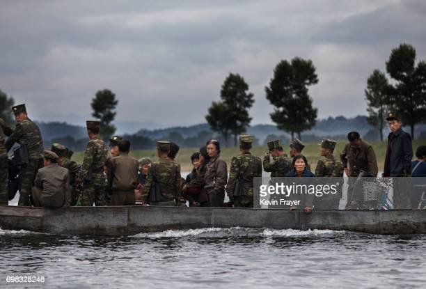 North Koreans ride on a boat used as a local ferry as they cross the Yalu river north of the border city of Dandong, Liaoning province, northern...