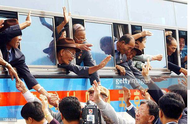 North Koreans stick their arms out from bus windows to hold the hands of their South Korean relatives as they bid farewell following the end of the...