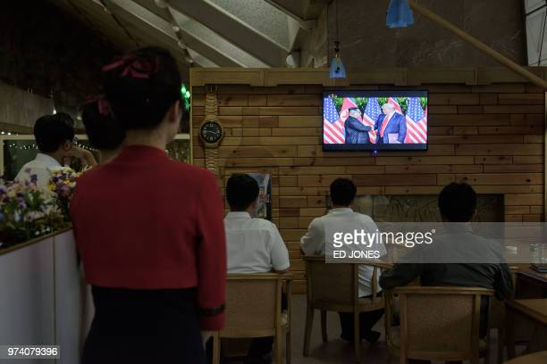 TOPSHOT North Koreans watch a television screen showing footage of North Korean leader Kim Jong Un attending a summit in Singapore with US President...