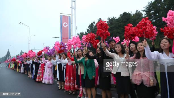 North Koreans wave bouquets on a street as a motorcade of South Korean President Moon Jaein makes its way to Pyongyang Sunan International Airport as...