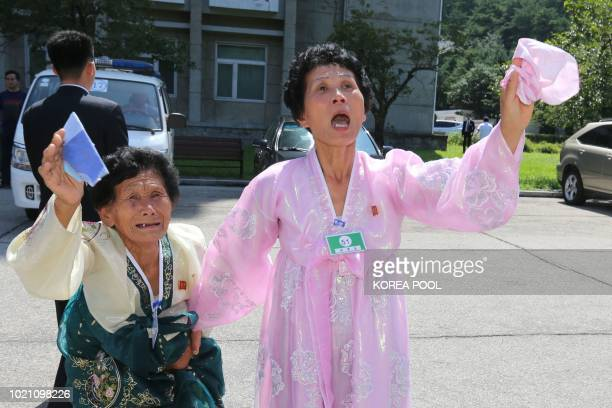 North Koreans wave farewell to their South Korean relatives after a three-day family reunion event at North Korea's Mount Kumgang resort on August...