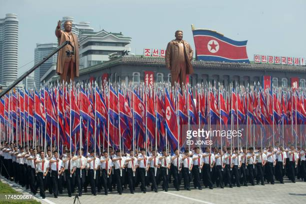 North Koreans wave flags and walk with statues of former leaders Kim IlSung and Kim JongIl during a military parade past Kim IlSung square marking...