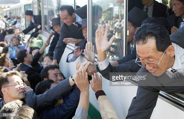 North Koreans wave goodbye to South Korean relatives after a family reunion at a resort on September 22 2003 in Diamond Mountain North Korea 453...