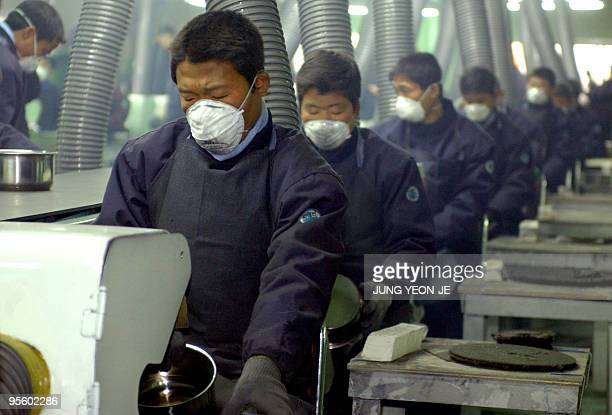 North Koreans work at the factory of Living Art a kitchenware maker which became the first South Korean firm to start production in a joint...
