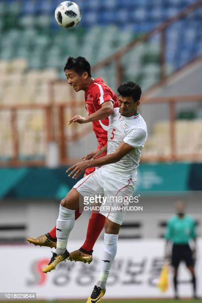 North Korea's An Song Il vies for the ball with Iran's Alireza Arta during the men's Group F football match between Iran and North Korea at the 2018...