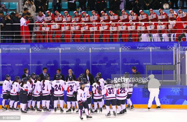 TOPSHOT North Korea's cheerleaders hold the Unified Korea flag and cheer after the women's preliminary round ice hockey match between Switzerland and...