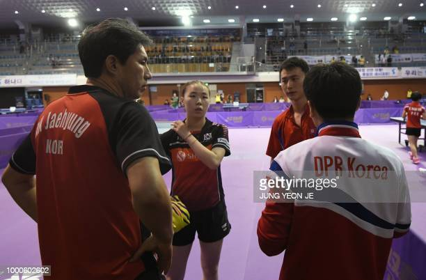 North Korea's Choe Il and his partner South Korea's Yoo Eunchong listen to their coaches during their preliminary round match against Spain's Alvaro...