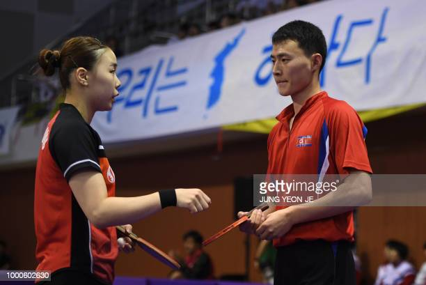 North Korea's Choe Il and his partner South Korea's Yoo Eunchong talk during their preliminary round match against Spain's Alvaro Robles and Galia...