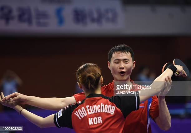 North Korea's Choe Il and his partner South Korea's Yoo Eunchong celebrate their victory against Spain's Alvaro Robles and Galia Dvorak during their...