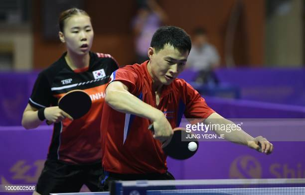 North Korea's Choe Il returns the ball as his partner South Korea's Yoo Eunchong looks on during their preliminary round match against Spain's Alvaro...