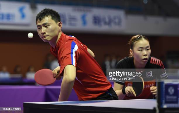 North Korea's Choe Il serves the ball as his partner South Korea's Yoo Eunchong looks on during their preliminary round match against Spain's Alvaro...