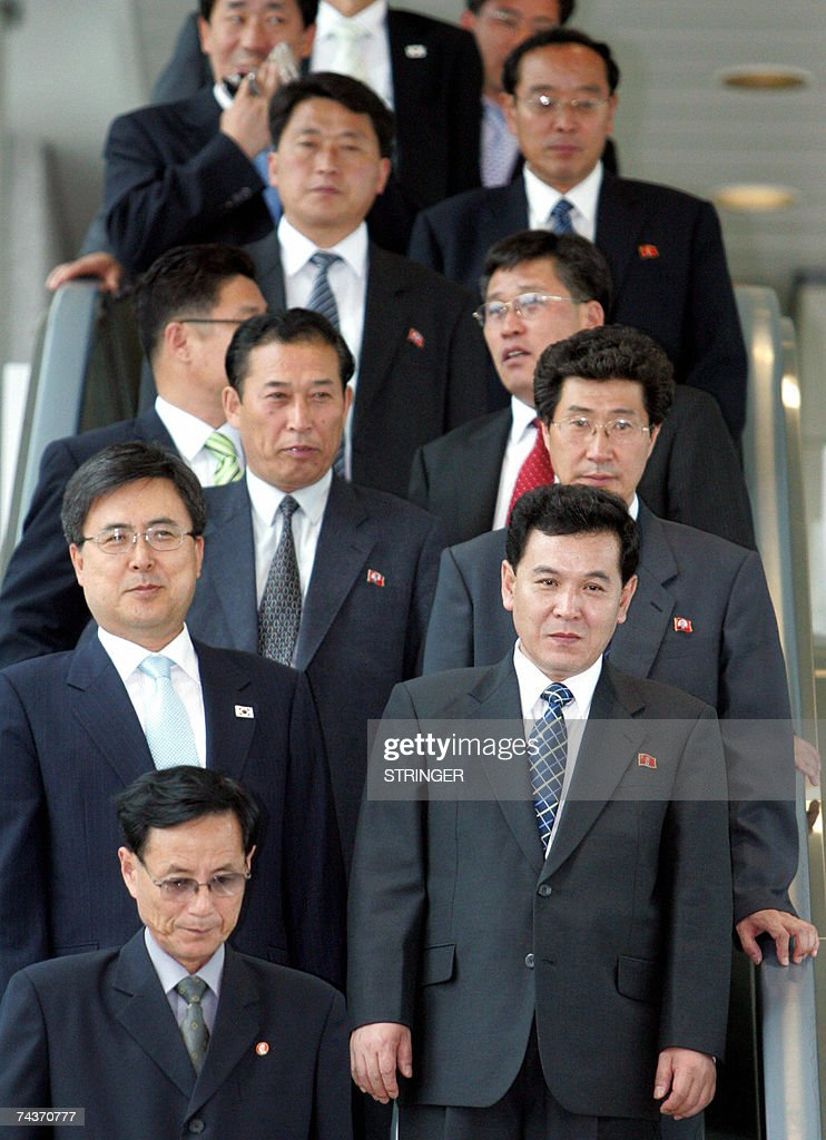 North Korea's delegation head and Senior Cabinet Councilor Kwon Ho Ung (2nd row R) and other delegation ride on a escalator at Incheon International Airport, west of Seoul, 01 June 2007. South Korea insisted it would withhold food aid to the North until its communist neighbor starts dismantling its nuclear weapons program, forcing their high-level reconciliation talks to end 01 June with no substantial agreement. AFP PHOTO/Ahn Young-joon/POOL